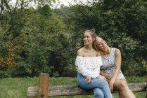 Zwei glückliche junge Frauen sitzen auf Zaun im Park — Stockfoto