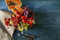 Papayasalat, Granatapfel, Salat, Tomaten, Oliven und Endivien auf blauem Holz — Stockfoto