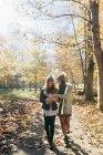 Deux femmes avec téléphone portable marchant dans la forêt automnale — Photo de stock