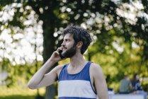 Мужчина разговаривает по мобильному телефону в парке — стоковое фото