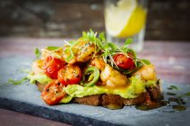 Crostini with shrimps and tomatoes, roasted bread, herbs, avocado cream, sweet chili sauce, jalapenos, cress — Stock Photo