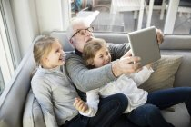 Due ragazze felici e nonno sul divano a farsi un selfie con tablet — Foto stock