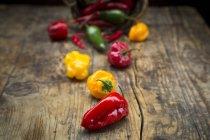 Poivrons frais et colorés éparpillés sur une table rustique en bois avec panier — Photo de stock