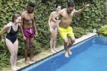 Щасливі друзів стрибати в басейн — стокове фото