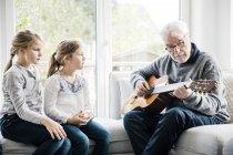 Две девочки сидят на диване и слушают, как дедушка играет на гитаре — стоковое фото