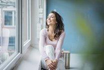Donna felice che guarda fuori dalla finestra — Foto stock