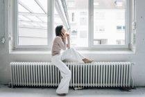 Femme riante au téléphone assis sur le chauffage dans le grenier — Photo de stock