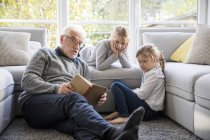 Two girls and grandfather reading book in living room — Stock Photo