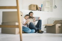 Couple sitting in new home surrounded by cardboard boxes and looking at tablet — Stock Photo