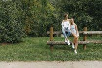 Duas jovens mulheres sentadas na cerca no parque — Fotografia de Stock