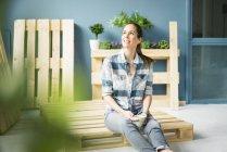 Schöne Frau, die eine Pause von der Renovierung ihres Hauses mit Paletten macht, Kaffee trinkt — Stockfoto