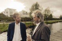 Dois homens de negócios conversando no lago — Fotografia de Stock
