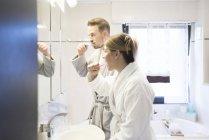 Couple se brossant les dents dans la salle de bain à la maison — Photo de stock