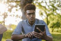 Молодой африканский американец смотрит на сотовый телефон в парке — стоковое фото
