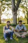 Два мультикультурных друга сидят в парке с мобильным устройством и бумагами — стоковое фото