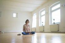 Зрелая женщина сидит на полу в пустой комнате и использует планшет — стоковое фото
