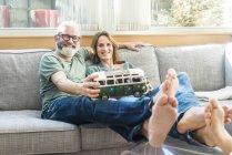 Щаслива Зріла пара на дивані на будинку холдингу мікроавтобус модель — стокове фото