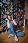 Расслабленная зрелая женщина слушает музыку перед ассортиментом ковриков для йоги — стоковое фото