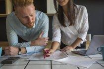 Uomo e donna con laptop che studiano i piani sul tavolo a casa — Foto stock