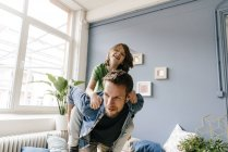 Happy father giving piggyback to son at home — Stock Photo