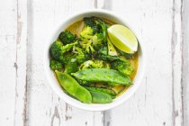 Green thai curry with broccoli, pak choi, snow peas, baby spinach, lime and rice — Stockfoto