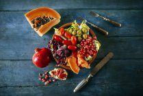Papaya salad, pomegranate, lettuce, tomato, olives and endive on blue wood — Stock Photo
