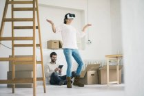 Couple in new home with woman wearing VR glasses — Stock Photo