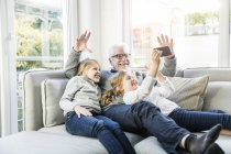Two happy girls and grandfather on sofa taking a selfie — Stock Photo