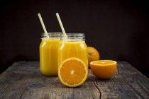 Freshly squeezed orange juice in jars with straws — Stock Photo