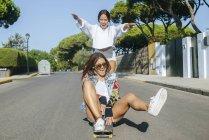 Два сміху друзів разом на скейтборді — стокове фото