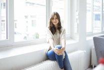 Портрет улыбающейся женщины, сидящей на обогревателе в светлой комнате с окном — стоковое фото