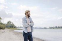 Красивый мужчина стоит у реки и держит руки скрещенными — стоковое фото