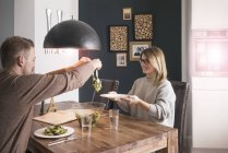 Couple eating salad at dining table at home — Stock Photo