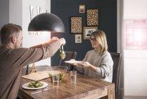 Pareja comiendo ensalada en la mesa de comedor en casa - foto de stock