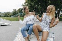 Два щасливих молодих жінок позує в скейтпарк — стокове фото