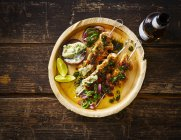 Grilled chicken skewers and garlic mayonnaise on plate, beer bottle — Photo de stock
