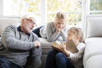 Dos niñas y abuelo leyendo libro en la sala de estar - foto de stock