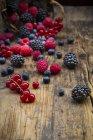 Diverse bacche estive sparse su tavolo in legno con cesto — Foto stock