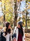 Deux jolies femmes qui se sourient dans une forêt automnale — Photo de stock