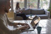 Uomo con laptop e donna con tablet a casa — Foto stock