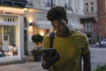 Americano africano do homem que olha a tabuleta na cidade no crepúsculo — Fotografia de Stock