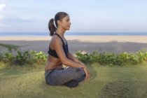 Indonesia, Bali, woman sitting on meadow in lotus position — Stock Photo