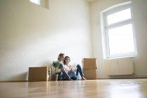 Coppia matura seduta al piano in camera vuota accanto a scatole di cartone e utilizzando tablet — Foto stock