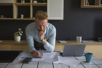 Uomo con computer portatile che studia i piani sul tavolo a casa — Foto stock