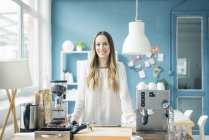 Portrait of happy young businesswoman in kitchen of a loft — Stock Photo
