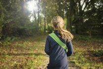 Вид сзади на девушку в лесу — стоковое фото