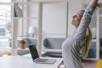 Женщина с ноутбуком за столом в офисе растяжения — стоковое фото