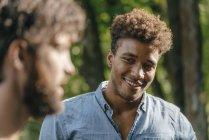 Молодой африканский американец улыбается другу — стоковое фото