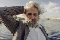 Портрет серьезного пожилого человека у озера — стоковое фото