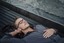Портрет молодого бизнесмена, отдыхающего на скамейке — стоковое фото